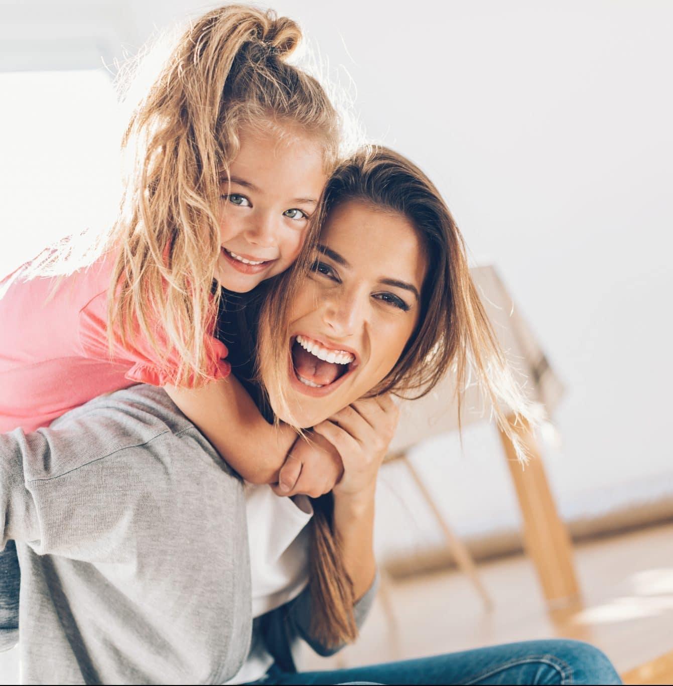 Mãe com filha às cavalitas