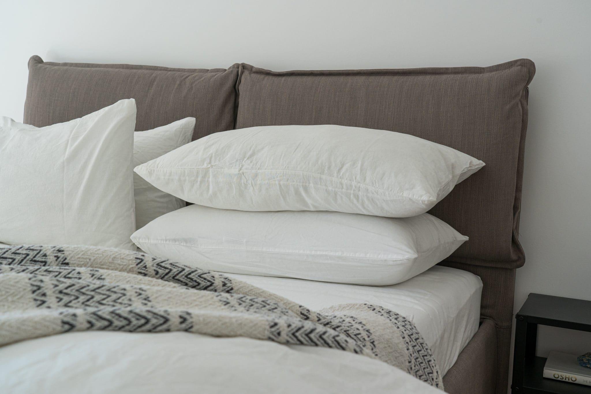 Conjunto de almofadas brancas em cama